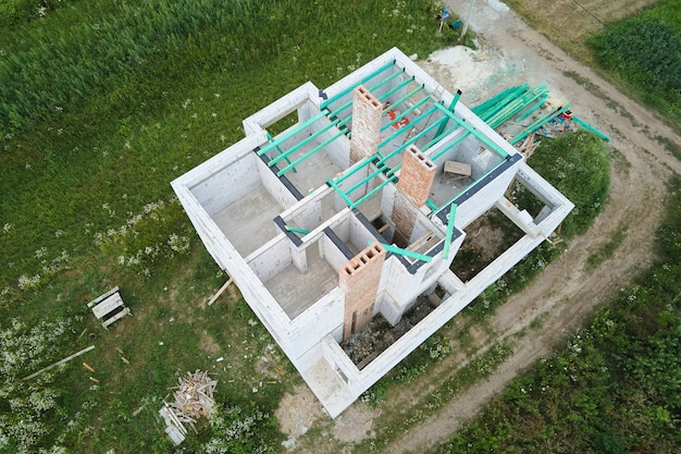 Aerial view of unfinished frame of private house with aerated lightweight concrete walls and wooden roof beams under construction.