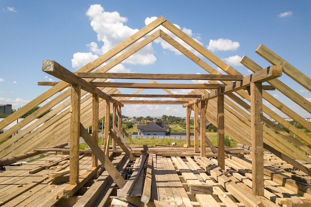 Aerial view of unfinished house with wooden roof frame structure under construction.