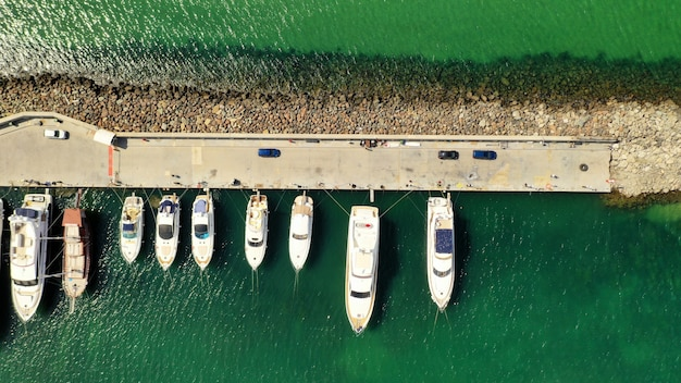 Aerial view of various types of boats docked near the coast at the sea