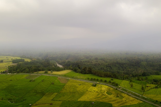 Aerial view of a village in the rainy season and fog on mountains and forests in indonesia