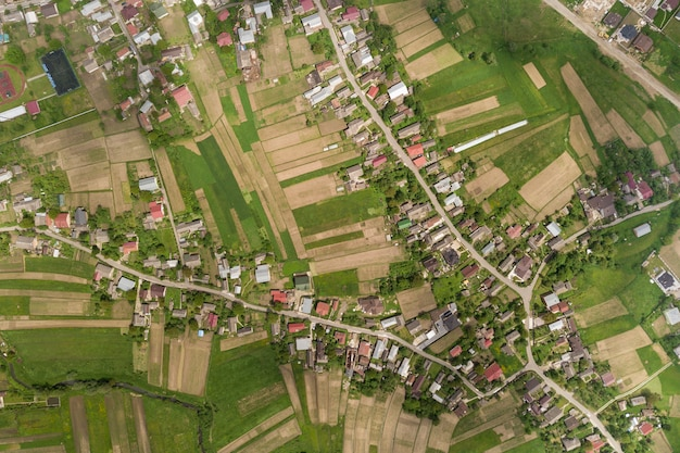 Aerial view of village with rows of buildings and curvy streets between green fields
