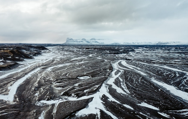 Aerial view of the volcanic desert on iceland in the background a glacier black rock filming loca