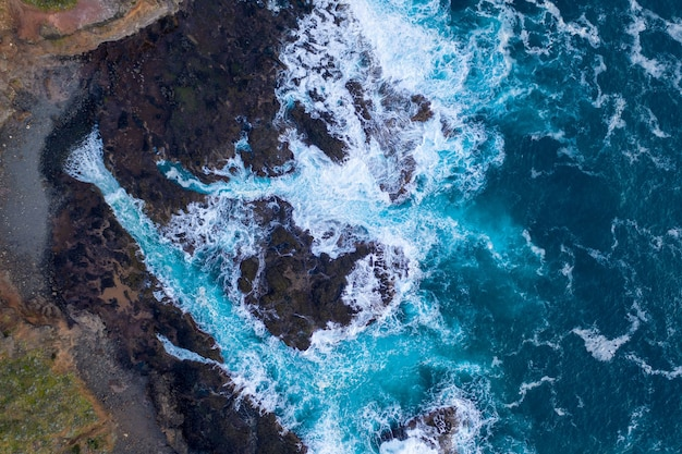 Aerial view of waves crashing on rocks