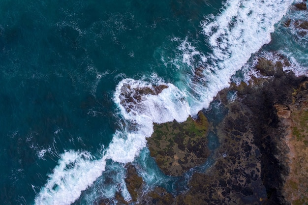 Aerial view of waves crashing on rocks