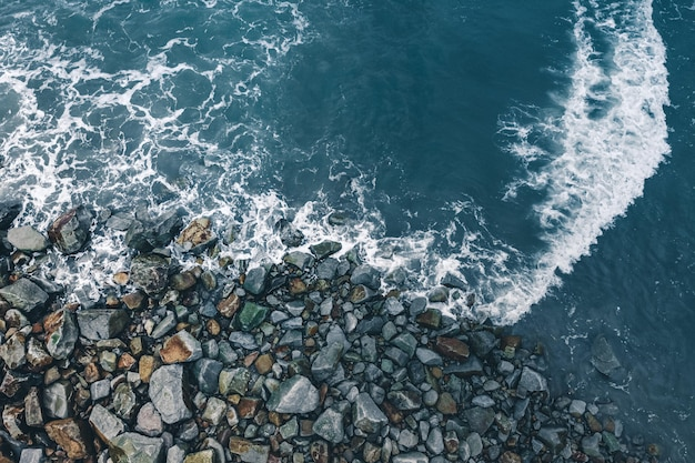 Aerial view of the waves of the ocean crashing on the rocks