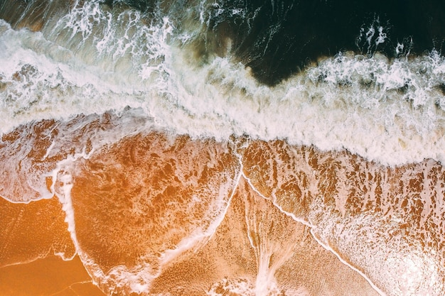 Aerial view of the waves of the sea crashing on the sandy beach