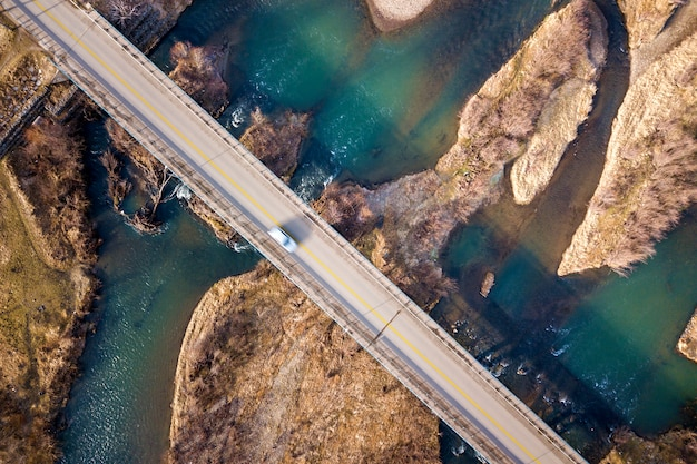 Aerial view of white bridge with moving car over blue water