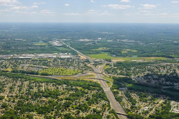 Облака вида с воздуха белые над деревней городка с строками зданий и curvy улицами между зелеными полями в лете.
