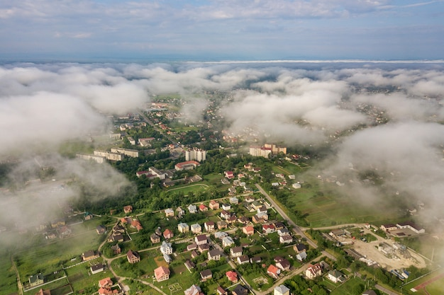 Aerial view of white clouds above a town or village with rows of buildings and curvy streets between green fields in summer. countryside landscape from above.