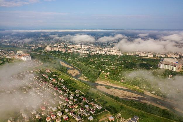 Aerial view of white clouds above a town or village with rows of buildings and curvy streets between green fields in summer.