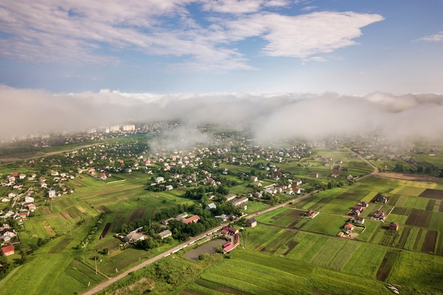 Aerial view of white clouds above a town or village with rows of buildings and curvy streets between green fields