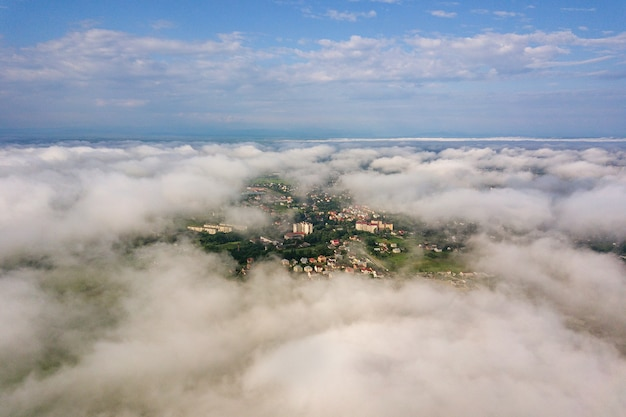 Aerial view of white clouds above a town or village with rows of buildings and curvy streets
