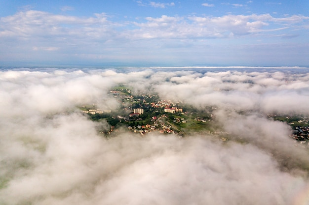 Aerial view of white clouds above a town or village with rows of buildings