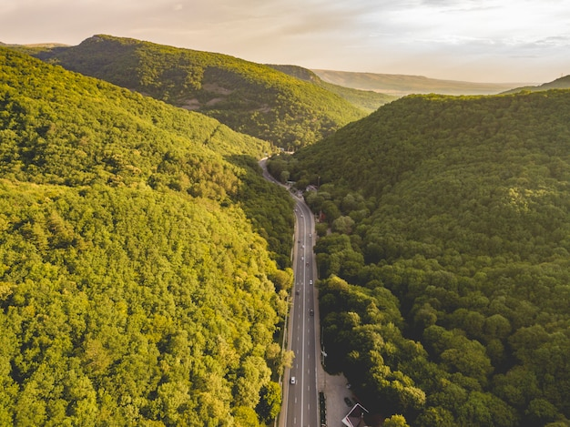 Aerial view of wide highway between the mountains covered with green woods