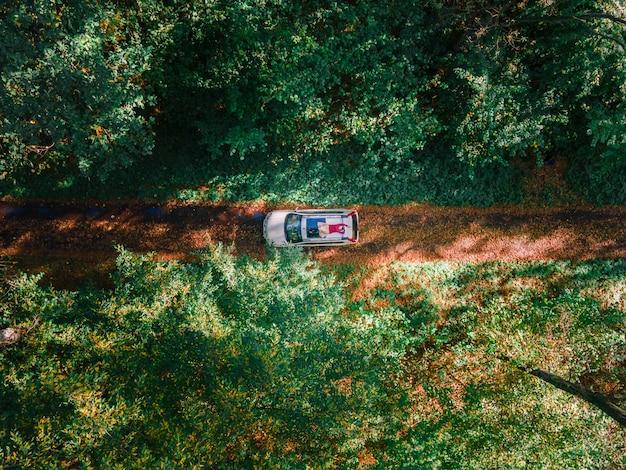 森のトレイル道路コピースペースの真ん中にsuv車の屋根に横たわっている空撮女性