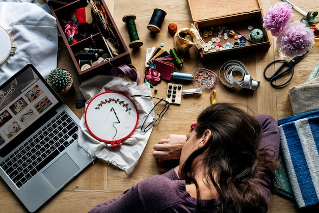 Aerial view of woman taking a nap on wooden table with handicraft work