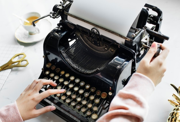 Aerial view of a woman typing on a retro typewriter blank paper