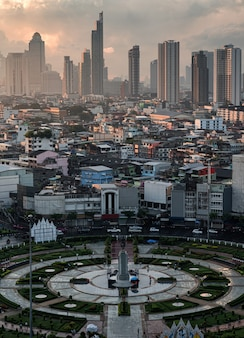 Aerial view of wongwianyai roundabout monument with crownded residence and skyscraper in downtown at bangkok, thailand