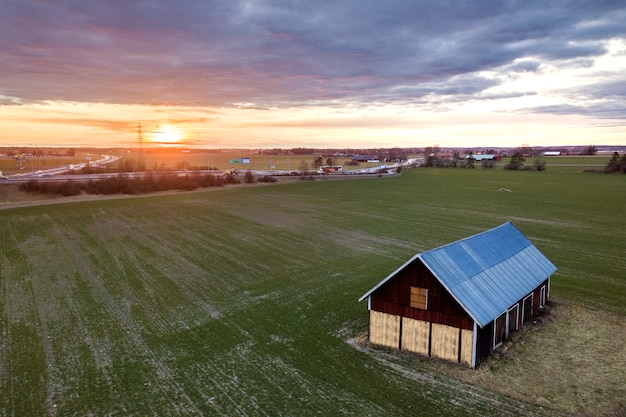 Aerial view of wooden barn in green field on  of modern highway road intersection at dawn on sunny spring day.