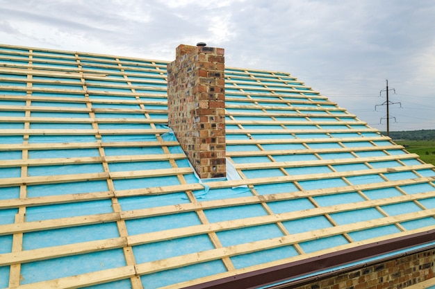 Aerial view of a wooden roof frame of brick house under construction.