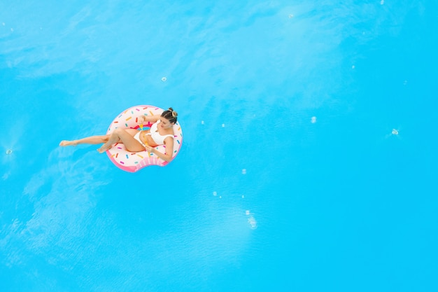 Aerial view of young beautiful girl in a white  bikini relaxing on inflatable donut in the pool. summer vacation background