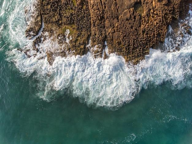 Aerial. waves break on the rocks from the sky. portugal algarve