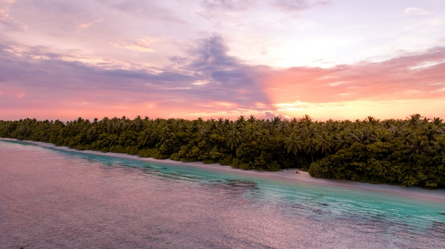 Aerial wide shot of a beach with trees next to the sea in maldives during sunset