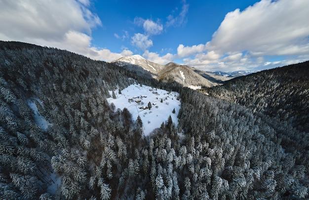 차가운 산의 눈 덮인 숲 사이에 작은 시골집이 있는 공중 겨울 풍경.