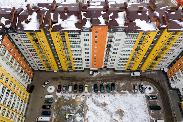 Aerial winter top view of tall apartment building, brick chimneys, tiled roof. urban infrastructure, view from above.