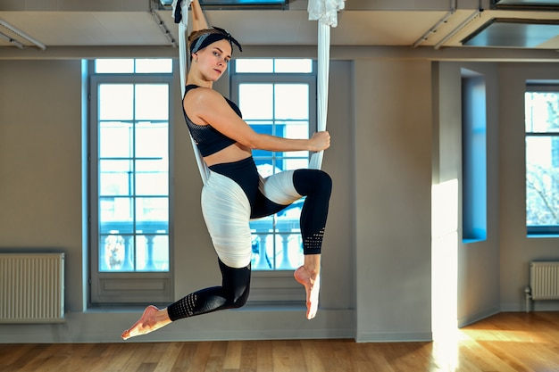 空中ヨガ美しい少女の空中ヨガトレーナーが、ヨガルームの吊り下げラインでさまざまな練習を行います。コンセプトヨガ、柔軟な体、健康的なライフスタイル、フィットネス。