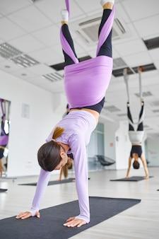 Занятия воздушной йогой, женские групповые тренировки, подвешивание на гамаках. фитнес, пилатес и танцевальные упражнения смешивают. женщины на тренировке йоги в спортивной студии