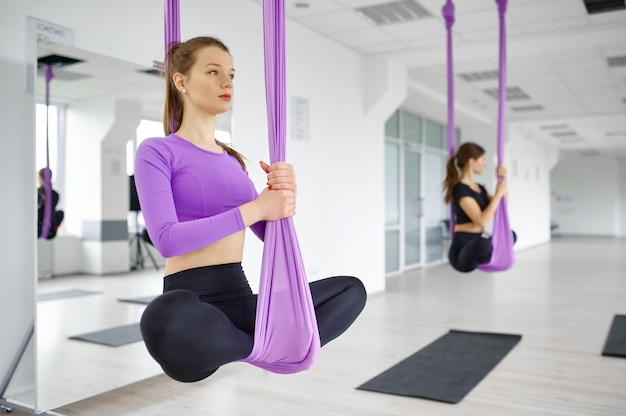 Воздушная йога, женские групповые тренировки, подвешивание на гамаках. фитнес, пилатес и танцевальные упражнения смешивают. женщины на тренировке йоги в спортивной студии