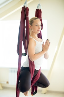 Aerial yoga: flying in hammock in baddha konasana pose