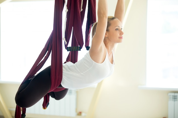 Aerial yoga: flying in hammock in butterfly pose