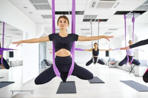 Воздушная йога, групповые занятия с гамаками. фитнес, пилатес и танцевальные упражнения смешивают. женщины на тренировке йоги в спортивной студии, здоровый образ жизни