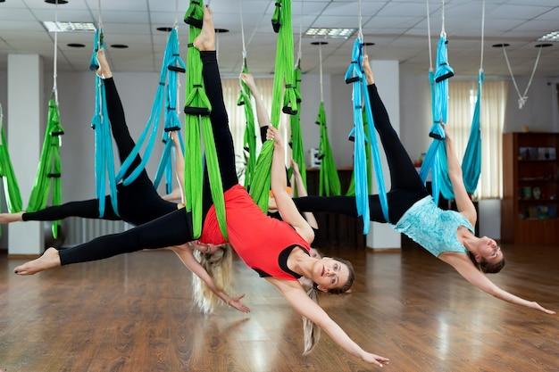 Воздушная йога в гамаке. худенькая спортивная женщина выполняет упражнения на гравитацию и растяжку. концепция здорового образа жизни