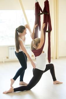 Инструктор по воздушной йоге, помогающий женщине делать низкую позу
