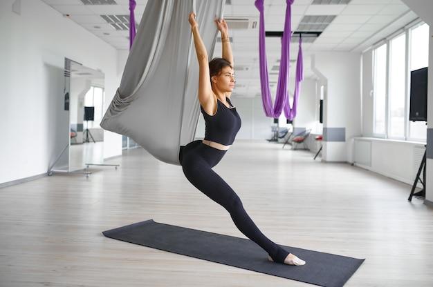Воздушная йога, стройная женщина на гамаке, растяжка. фитнес, пилатес и танцевальные упражнения смешивают. женский человек на тренировке йоги в спортивной студии