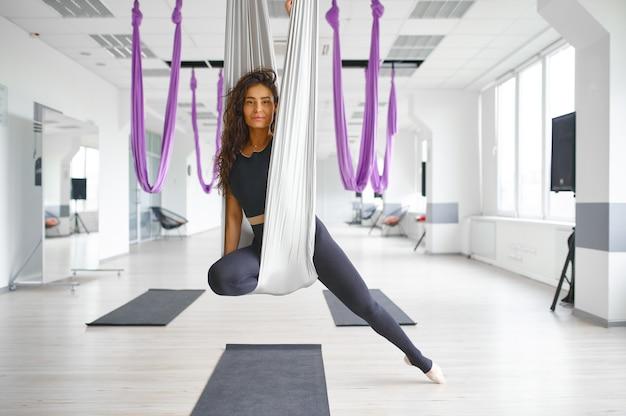 Воздушная йога, стройная женщина позирует на гамаке. фитнес, пилатес и танцевальные упражнения смешивают. женский человек на тренировке йоги в спортивной студии