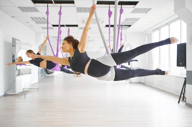 Студия воздушной йоги, женские групповые тренировки, подвешивание на гамаках. фитнес, пилатес и танцевальные упражнения смешивают. женщины на тренировке йоги в тренажерном зале