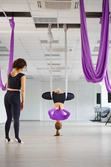 Воздушная йога, инструктор-женщина и женщина, обучение в гамаках. фитнес, пилатес и танцевальные упражнения смешивают. женщины на тренировке йоги в спортивной студии