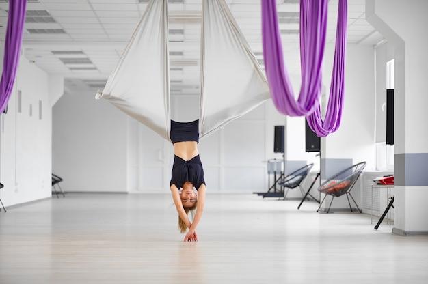 Воздушная йога, женщина висит вверх ногами на гамаке. фитнес, пилатес и танцевальные упражнения смешивают. женский человек на тренировке йоги в спортивной студии