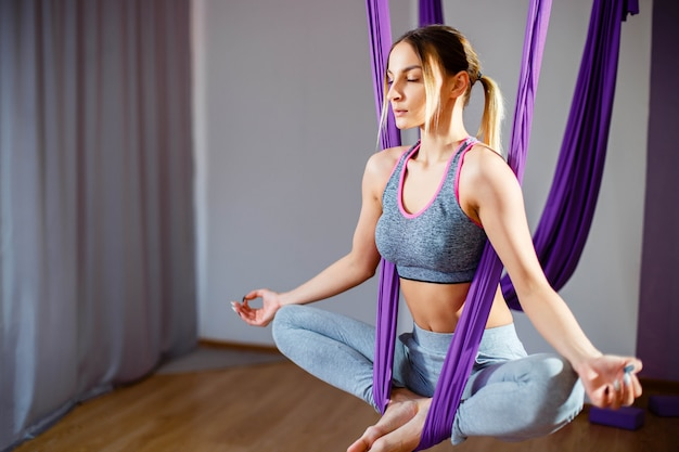 Портрет молодой женщины, делающей антигравитационные упражнения йоги. aero aero fly фитнес-тренер тренировки