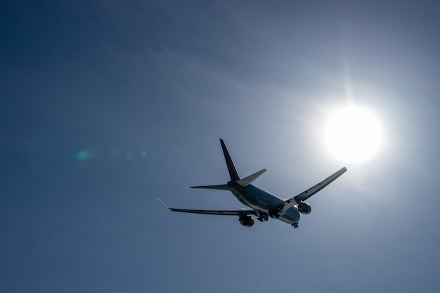 Aero plan take off from airport with view of the direct sun and blue sky.
