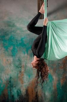 Аэро-йога молодая женщина занимается йогой или растягивается на подвеске