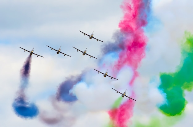 Aerobatic team aircraft fighters trail of smoke in the sky.