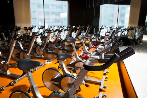 Aerobics spinning exercise bikes gym room in a row
