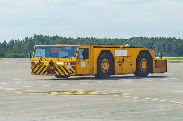 The aerodrome tractor is driving along the steering paths at the airport.