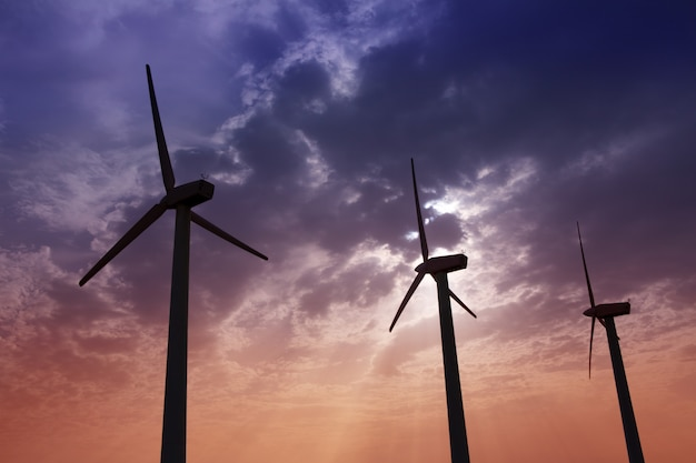 Aerogenerator windmills on dramatic sunset sky