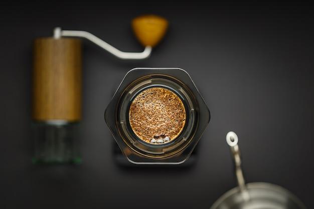 Кофеварка aeropress с весами, кофемолкой и чайником на вид сверху черной поверхности.
